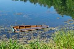 Bateau en bois submergé sur la rivière ou le lac près du rivage Images stock