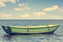Bateau en bois vert éloignant du rivage à la mer Image stock