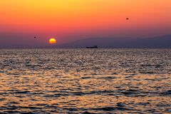 Bateau en mer pendant le beau coucher du soleil images stock