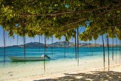 Bateau et arbres sur une plage tropicale aux Fidji Photographie stock libre de droits