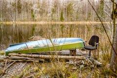 Bateau et chaise sur la côte du lac sauvage photos stock