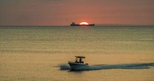 Bateau et coucher du soleil de sillage au-dessus des vues du Curaçao d'océan Photos stock