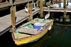 Bateau et pélicans de rangée colorés à un dock photos stock