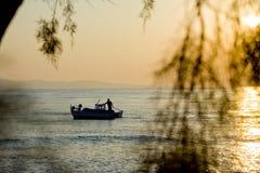 Bateau et palmier de coucher du soleil Photographie stock libre de droits