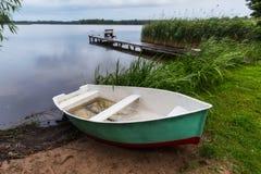 Bateau et pont du ` s de pêcheur avec des poteaux de pêche au lac Masuria, photo libre de droits