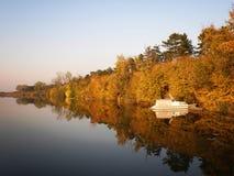 Bateau et rivière en automne avec les arbres colorés photo stock