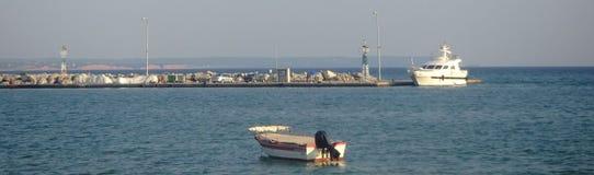 Bateau et un bateau blanc dans un port Images libres de droits