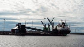 Bateau finlandais dans le port de cargaison pendant l'op?ration de cargaison Bateau travaillant au gasoil image libre de droits