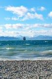 Bateau flottant sur le fond de montagnes Photos libres de droits