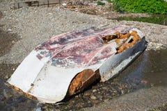 Bateau inversé abandonné se trouvant sur le rivage de la coque endommagée images stock