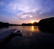 Bateau isolé sur la rivière avec le coucher du soleil photographie stock libre de droits