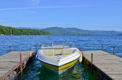 Bateau jaune au dock sur un lac Image libre de droits