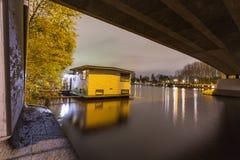 Bateau-maison situé sous un pont en rivière d'Amstel à Amsterdam Photos libres de droits