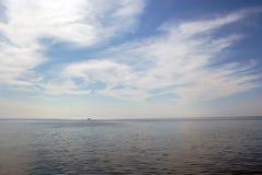 Bateau minuscule dans l'horizon sous le ciel nuageux Photographie stock