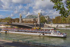 Bateau Mouche, Paris. Bateau Mouche going under the Napoleon III bridge in Paris with exposition hall in background Stock Images