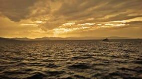 Bateau recherchant la couverture devant une tempête qui construit sur la mer Méditerranée Photographie stock