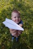 Bateau riant heureux de papier de prise d'enfant à l'intérieur Fond vert de champ Enfance heureux, été, vacances, voyage, concept photographie stock libre de droits