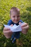 Bateau riant heureux de papier de prise d'enfant à l'intérieur Fond vert de champ Enfance heureux, été, vacances, voyage, concept image libre de droits
