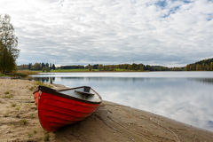 Bateau rouge sur le rivage de lac Image stock
