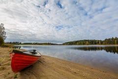 Bateau rouge sur le rivage de lac Photographie stock
