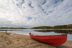 Bateau rouge sur le rivage de lac Images stock