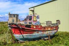 Bateau rouillé coloré devant un hall d'usine, Irlande photos stock