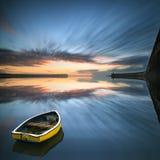 Bateau simple ne flottant aucune eau pendant le lever de soleil au-dessus de la mer avec la lumière Image stock