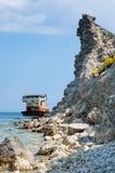 Bateau submergé rouillé parmi les roches de mer Photos stock