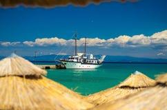 Bateau sur l'eau bleue de paradis du golfe de kolpos de Toroneos, Halkidiki, photographie stock