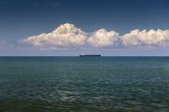 Bateau sur l'horizon et le grand cumulus photographie stock libre de droits