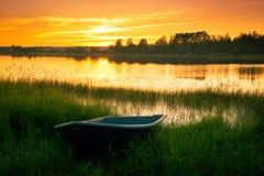 Bateau sur la banque de la rivière au coucher du soleil dans l'herbe Photos stock