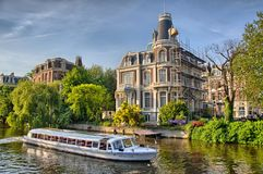 Bateau sur la rivière d'Amstel près de belles maisons à Amsterdam, Hollande, Pays-Bas, HDR image libre de droits