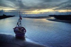 Bateau sur le rivage d'océan au coucher du soleil Image libre de droits