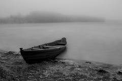Bateau sur le rivage près du lac congelé pendant l'hiver noir et blanc de brume photos stock