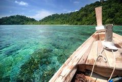 Bateau thaïlandais flottant sur l'eau claire au-dessus du récif photo libre de droits