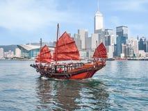 Bateau traditionnel d'ordure de rouge-voile de Hong Kong sur le CCB de gratte-ciel de ville Photographie stock