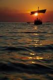 Bateau à voiles antique au coucher du soleil Image stock