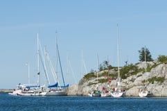 Bateaux à voile amarrés à un archipel de Stockholm de falaise Photos libres de droits