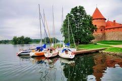 Bateaux à voile au château de Trakai Image stock