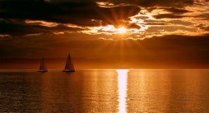 Bateaux à voile pendant les navires du coucher du soleil deux photos libres de droits