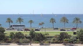 Bateaux à voile sur la mer, voitures sur la route et piétons sur le trottoir, en paysage de panorama de vue aérienne de ville de  banque de vidéos