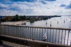 Bateaux à voile sur la réflexion de Sun de rivière du pont photographie stock