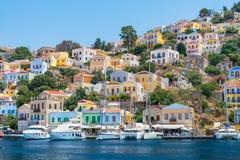 Bateaux à voile, yachts et maisons colorées dans la ville de port de l'île de Symi Symi, Grèce photographie stock