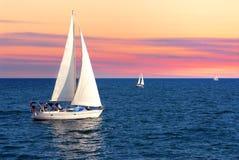 Bateaux à voiles au coucher du soleil photographie stock