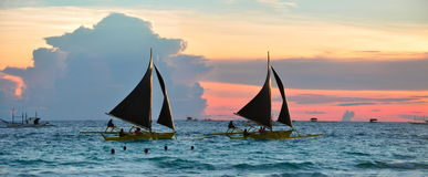 Bateaux à voiles contre le beau coucher du soleil Image stock