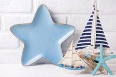 Bateaux, étoile de mer et plat décoratifs sous la forme de l'étoile tout près W Photos stock