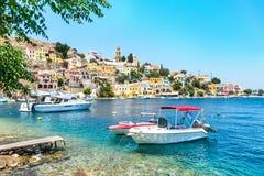 Bateaux ancrés et maisons néoclassiques colorées dans la baie de l'île de Symi Symi, Grèce photographie stock