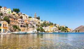Bateaux ancrés et maisons néoclassiques colorées dans la baie de l'île de Symi Symi, Grèce photo stock