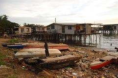 Bateaux avec des déchets à la côte de village de mer Images stock