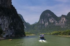 Bateaux avec des touristes croisant dans Li River près de la ville de Yangshuo en Chine Photographie stock libre de droits
